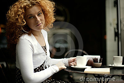 Gaze of a young woman in a street cafe