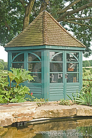 Gazebo beside fish pond in garden.