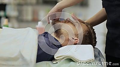 Gebaarde mens Gezichts drogen veegt af Masseer het gezicht en de hals Hyaluronic masker stock video