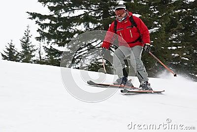 Gebirgsmann-Skifahrer, der unten die Steigung rollt