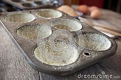 Gebuttertes Muffinzinn mit Maismehl