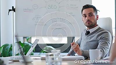 Geconcentreerde jonge zakenman die naar zijn partners luistert tijdens de vergadering over de samenwerking in de ruimte stock videobeelden