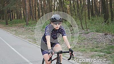 Geconcentreerde profietser vrouwelijke berijdende fiets in het park Het concept van de opleiding cycling Langzame Motie stock video