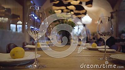 Gediende lijst in een duur restaurant Lege wijnglazen, witte platen, bestek op een houten lijst De sappige citroenen liggen stock footage