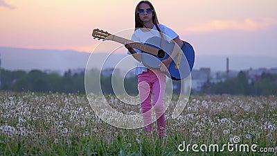 Gegen Hintergrund des lustigen Musikers des kleinen Mädchens der Stadtlandschaft auf der Sonnenbrille, welche die Gitarre und die stock video footage