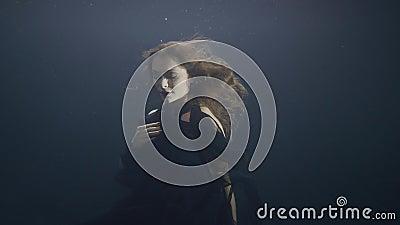 Geheimzinnige vrouw in zwarte kleding die als meermin onder water in donkere pool zwemmen stock videobeelden