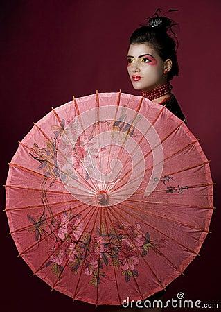 Geisha mit traditionellem gemaltem Regenschirm
