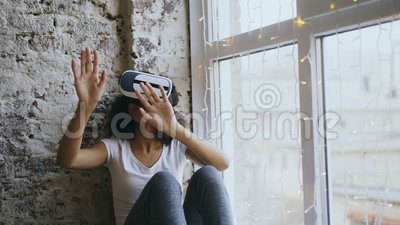 Gelockte Afroamerikanerfrau, die zu Hause Erfahrung unter Verwendung der Kopfhörergläser VR 360 virtueller Realität erhält stock footage