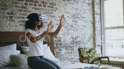 Gelocktes Mischrassejugendlichmädchen, das zu Hause Erfahrung unter Verwendung der Kopfhörergläser VR 360 virtueller Realität erh stock video