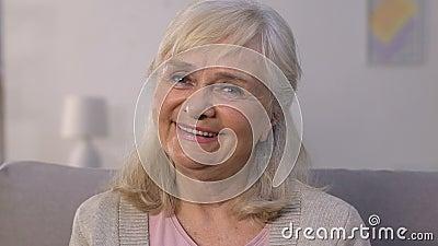 Gelukkig bejaard wijfje die en camera, ziektekostenverzekering, bescherming glimlachen bekijken stock footage