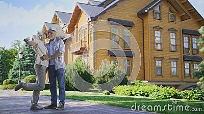 Gelukkig hoger paar die sleutels tonen aan nieuw groot huis stock footage