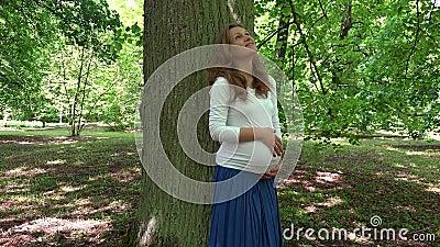 Gelukkig Kaukasisch zwanger meisje die haar buik strijken die zich dichtbij grote boomboomstam bevinden stock video