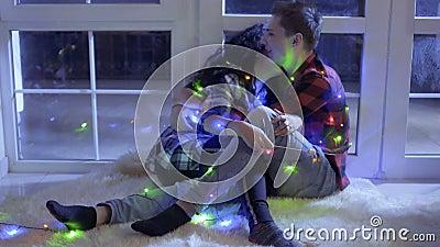 Gelukkig in liefdes verfraaide het paar kleurrijke slinger ontspant dichtbij venster op vloer stock footage
