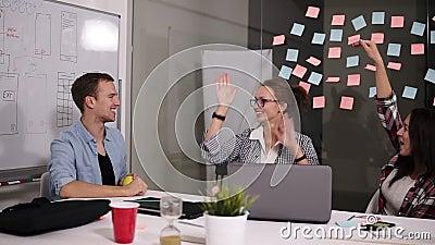 Gelukkig succesvol jongeren commercieel team die een hoog fivesgebaar geven aangezien zij lachen en hun succes bij project toejui stock footage
