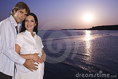 Gelukkig zwanger paar op strand bij zonsopgang