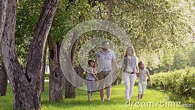 Gelukkige familie die in de zomerpark dichtbij de tot bloei komende Apple-bomen lopen de vader, de moeder en twee dochters brenge stock video