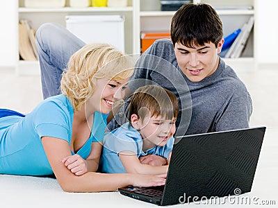 Gelukkige familie die in laptop samen kijkt