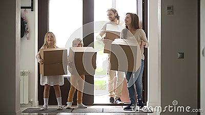 Gelukkige familie die met jonge geitjes dozen houden die deur openen die huis ingaan stock video