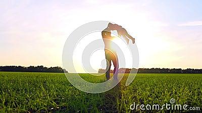 Gelukkige familie speelaard in het park bij zonsondergang De vader houdt zijn zoon door de wapens en draaien met hem in langzaam