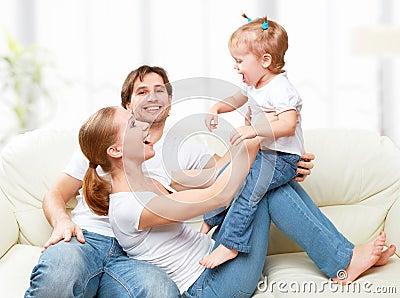 Gelukkige familiemoeder vader de dochter van de kindbaby thuis op en bank die spelen lachen - Bank thuis van de wereld ...