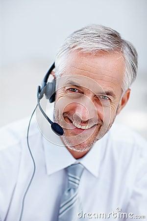 Gelukkige hogere mens die op de hoofdtelefoons spreekt