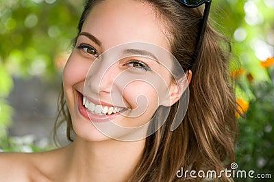 Gelukkige jonge donkerbruine vrouw met verbazende glimlach.