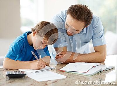 Gelukkige mens die zijn zoon helpt om thuiswerk te doen