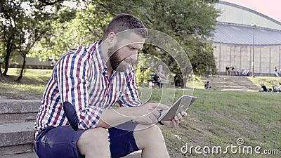 Gelukkige mens het doorbladeren tablet, die op treden zitten stock videobeelden
