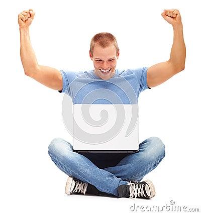Gelukkige mens met zijn omhoog wapens, gebruikend laptop