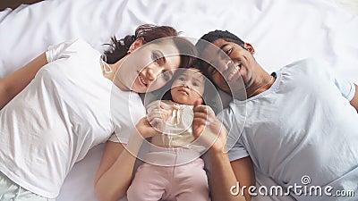 Gelukkige ouders die met leuk babymeisje thuis rusten in bed stock footage