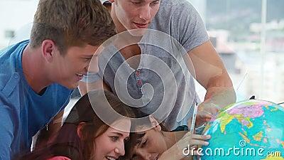 Gelukkige studenten die een bol bekijken stock video