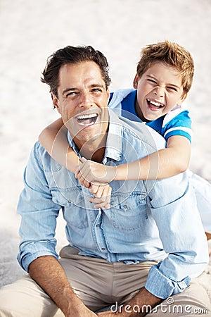 Gelukkige vader en zoon met grote glimlach bij het strand