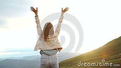 Gelukkige vierende winnende succesvrouw bij zonsondergang of zonsopgang status verrukt die met wapens omhoog boven haar hoofd bin stock video
