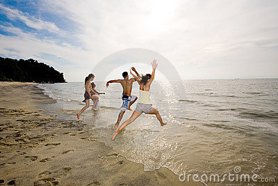 Gelukkige vrienden die pret hebben door het strand