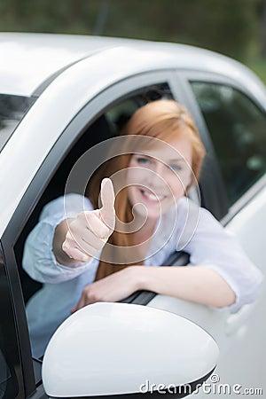 Gelukkige vrouw in het nieuwe auto geven duimen omhoog