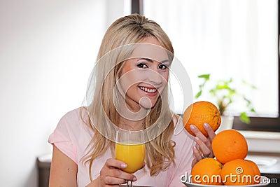 Gelukkige vrouw met sinaasappelen en sap