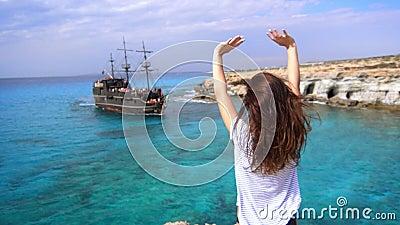 Gelukkige vrouw op kust verheugende aankomst van varend schip in baai stock footage