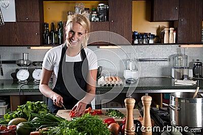 Gelukkige vrouwelijke chef-kok in de keuken