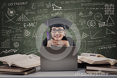 Gelukkige vrouwelijke gediplomeerde die gebruikend laptop bij klasse denken