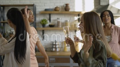 Gemengde racegroep van 5 vrouwelijke vrienden die plezier hebben in de keuken meisjes drinken champagne en dans 4K stock video