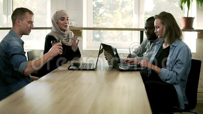 Gemischtrassige Gruppe Geschäftsleute, die im modernen hellen Büro sich treffen Junges Team, das über Fortschritt des Projektes s stock video