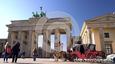 Gente, ciclistas, turistas caballo y carruaje durante el día en la Puerta de Brandenburgo, Pariser Platz, Berlín, Alemania almacen de metraje de vídeo