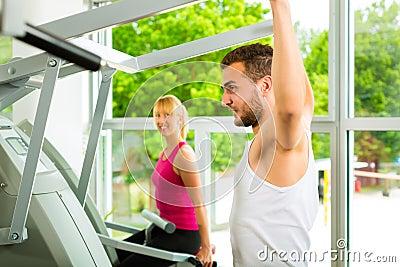 Gente en gimnasio del deporte en la máquina de la aptitud