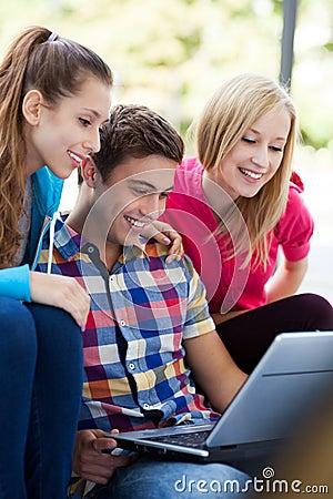 Gente joven que mira la computadora portátil junto