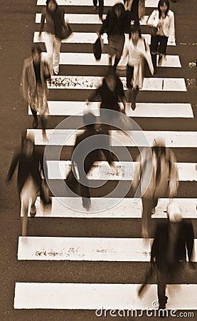 Gente que cruza los tonos de la calle-sepia