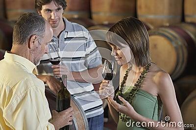 Gente que prueba el vino al lado de los barriles de vino