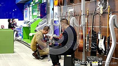 Gente que toca la guitarra dentro de la tienda de Best Buy metrajes