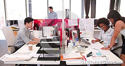 Gente que trabaja en los escritorios en oficina abierta moderna del plan