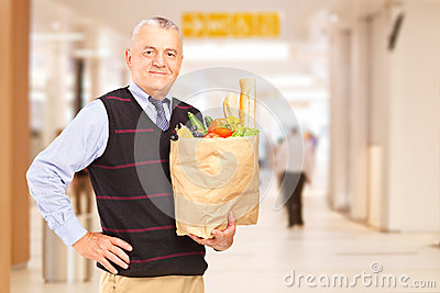 Gentelman in a shopping mall holding a paper bag