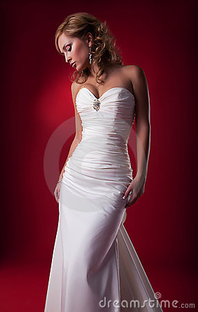 Gentle cute blonde bride posing in studio